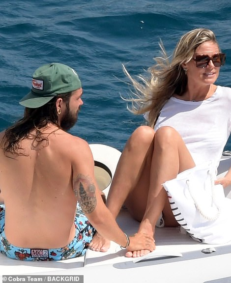 Loving: Tom tenderly caressed Heidi's feet as they continued to float along