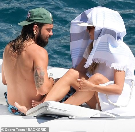Sizzling: When the heat got a little too much. Heidi put her baseball cap on her lover's head and covered up with a blanket to make sure she didn't get burned