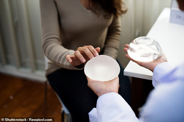 Women who suffer from severe pain due to hardening and shrinkage of the internal scar tissue ¿ known as capsular contracture ¿ may be eligible to have their implants removed on the NHS. Otherwise, they have to pay about £3,500 (pictured, a woman examines a breast implant)