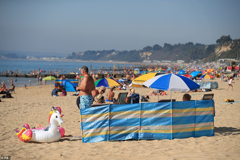 An inflatable unicorn float rests on the sand ready to be used when this family take a trip in to the sea in Bournemouth