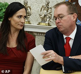 Look sharp: Stephanie Grisham and Mick Mulvaney appeared to pass notes as Trump spoke to reporters