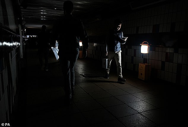 Rail passengers use the light of their phones to get through a dark tunnel beneath Clapham Junction station during the power cut on August 9