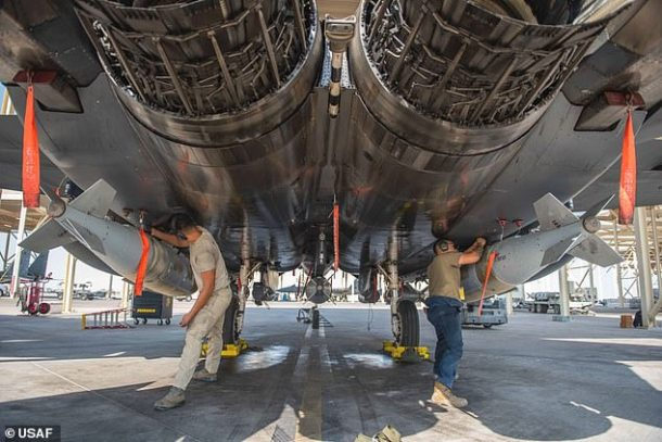 Laser-guided JDAM bombs are fitted to the underside of an F-35 fighter jet as it prepares to take part in a bombing run on Qanus Island