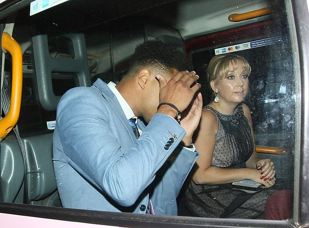Heading home: The soap star covered his face with his hands as he sat in the taxi with a female friend
