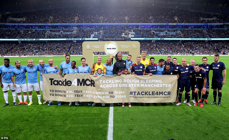Kompany and several big-name starshold up a banner for the Tackle4MCR campaign prior to the City legend's testimonial