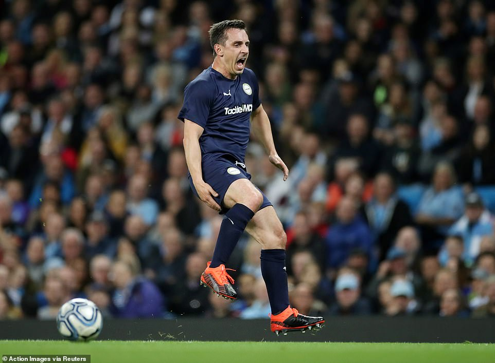 Manchester United legend and Sky Sports pundit Gary Neville pulls his hamstring during the first half at the Etihad