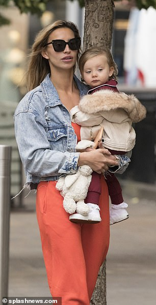 Mini style queen: Little Sunday looked adorable in a burgundy dress and a beige coat with a faux fur hood draped over her shoulders, while carrying her favourite cuddly bunny