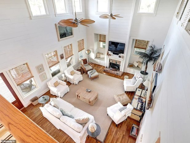 The open-plan living area has a chimney and is decorated with a nautical theme with all white walls and wicker furniture