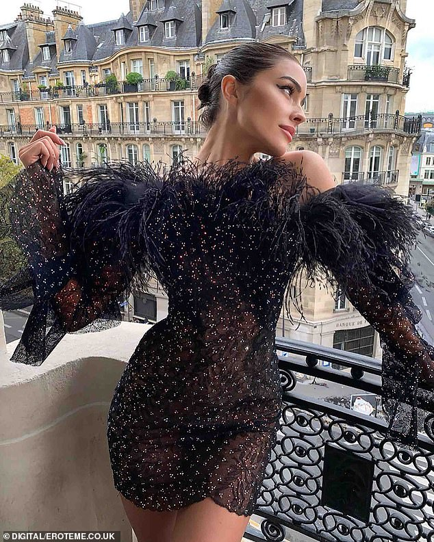 French chic: After making a Parisian street her own runway, Olivia posed up a storm on her hotel balcony - complete with a view of beautiful building behind her