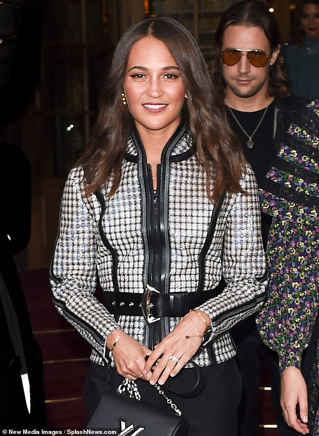 Chic: Alicia, 30, showcased her trim frame in a striking monochrome check jacket with leather zip detail and a matching leather belt across the midsection.
