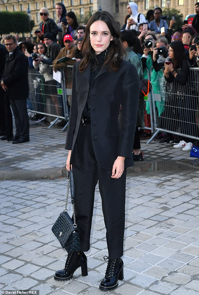 Chic: Actress Stacy Martin wowed in a sharply tailored black suit as she posed at the show