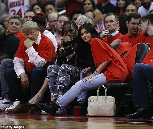 Cosy: Travis and Kylie first met at Coachella in April 2017 and immediately began dating,later spotted holding hands at a Houston Rockets NBA playoff game (pictured)