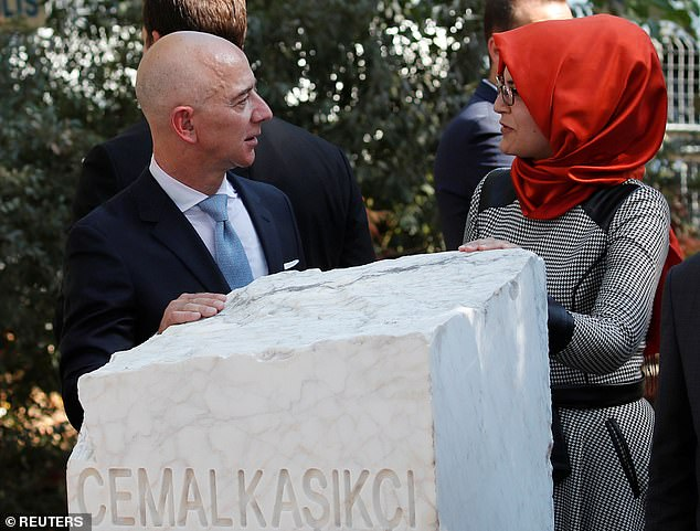 Bezos and Cengiz stand over a memorial stone for Khashoggi in Istanbul today. The death remains shrouded in mystery and Khashoggi's body has never been found