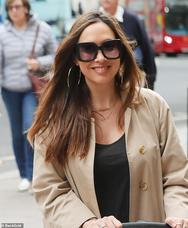 Glam: The mother-of-three looking effortlessly chic in a beige mac and oversized sunglasses, which glammed up the rest of her, much more casual, attire