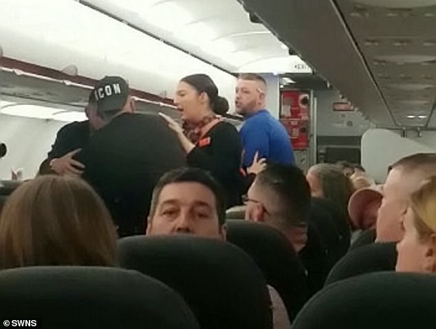 A passenger on board the easyJet flight from Manchester to Tenerife captured the row near the back of the plane where an air stewardess attempting to break up the fight