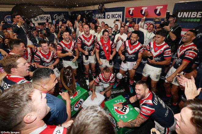 An elated Roosters side celebrate victory with the trophy in the changing rooms after Sunday night's Grand Final