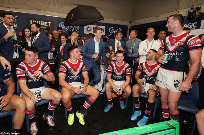 Steve Smith (centre) shares a beer with Roosters captain Boyd Cordner and other players in the changing room