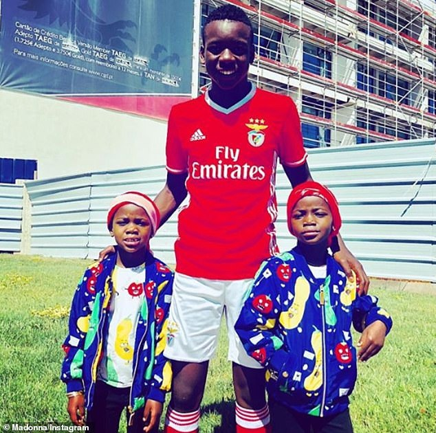Close bond: Sporty teenager David, who was adopted by Madonna from Malawi in 2006, is seen with his twin sisters Stella and Esther, six
