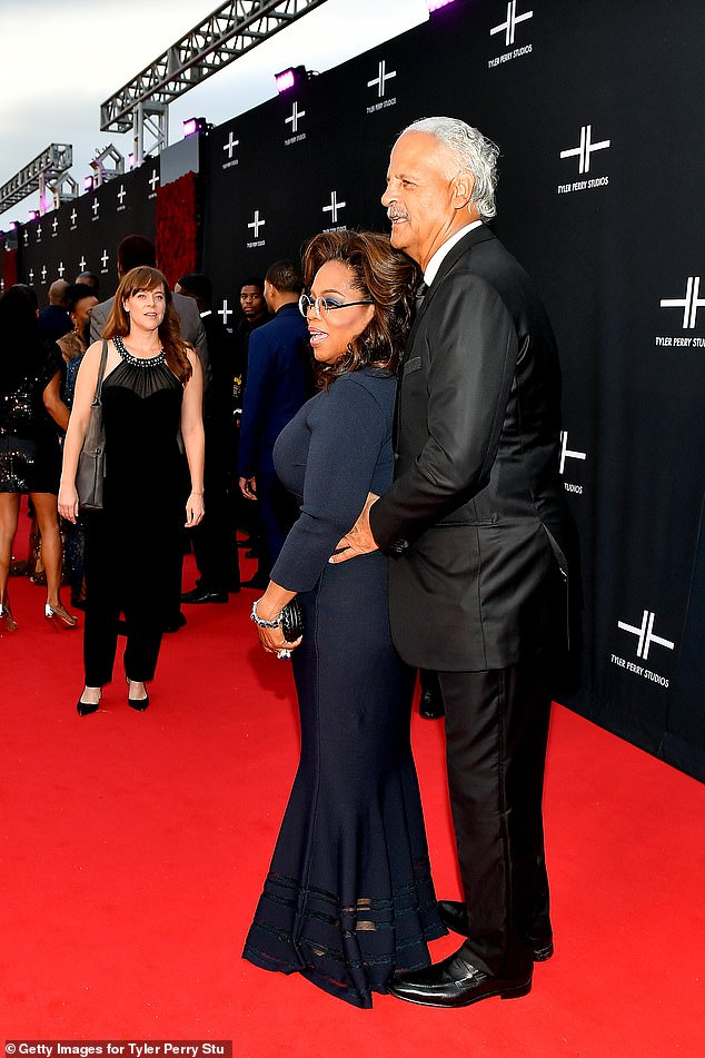 Chic OW: Oprah looked slender in her long dark blue dress that had long sleeves and a mermaid finish with sheer panels. She added black heels and carried a matching clutch purse