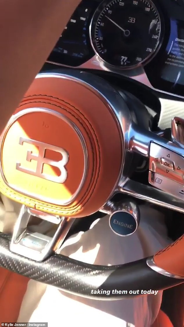 Stunning: She proudly showed off the steering wheel complete with the Bugatti logo