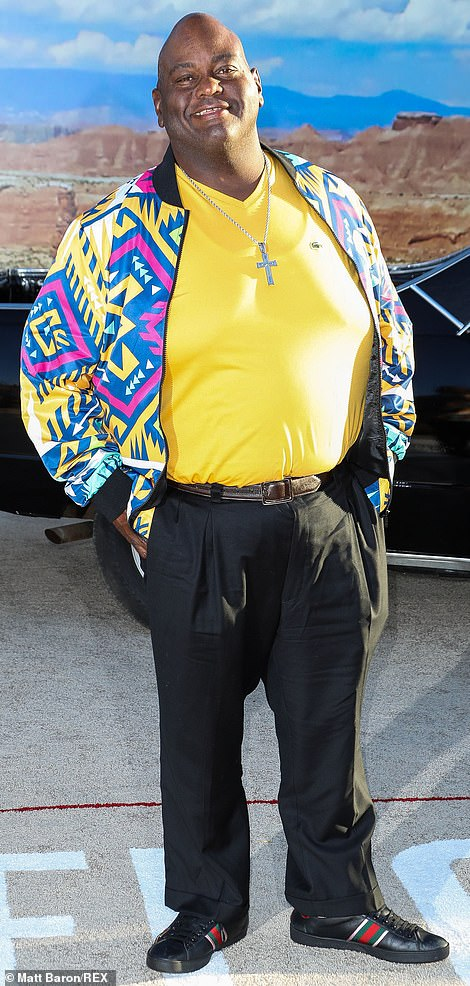 Splash of color: Lavell Crawford brought a splash of color to the red carpet with a yellow, blue and purple Aztec print bomber jacket over a yellow v-neck t-shirt