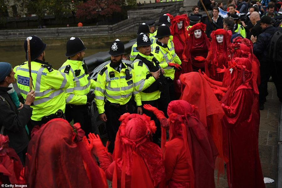 The Red Brigade of The Invisible Circus surround police in Westminster yesterday on the first day of XR chaos in London