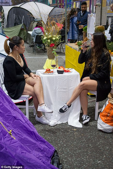 Two women appear to enjoy a glass of wine and a meal of tomatoes and peppers this morning after occupying Smithfield Market