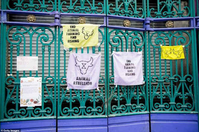 Signs are pictured on the entrance gates to Smithfield Market in east London demanding an end to animal farming and fishing. Protestors want the Government to turn Smithfield into a 'plant-based emporium