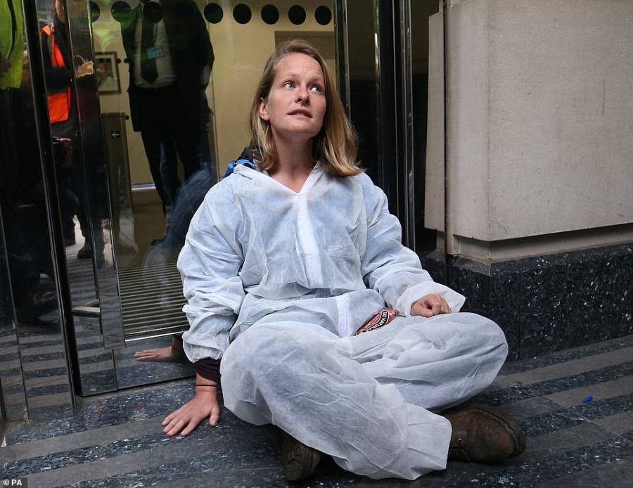 His comrade appeared to have glued her hand to the floor as activists plan to disrupt every Government department's building