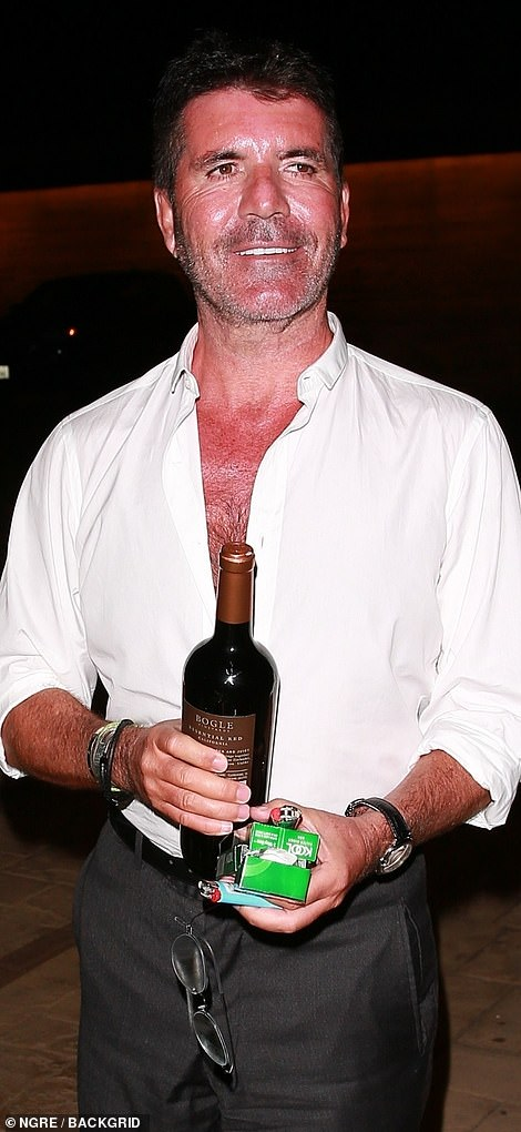 Celebrating! Simon rocked an unbuttoned shirt and loose trousers for this big night out in Malibu