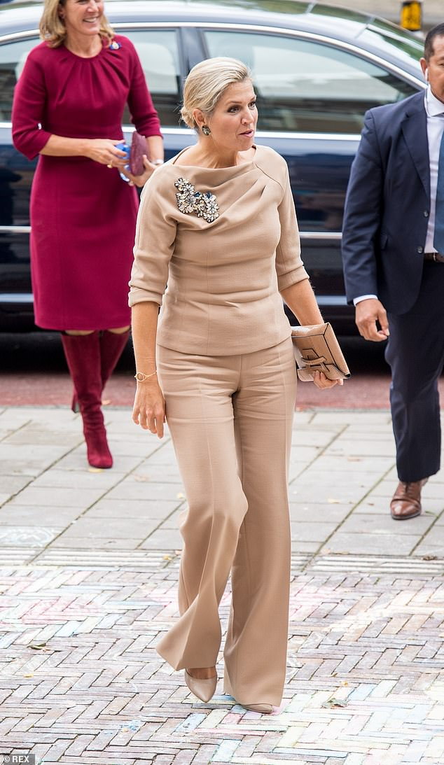 The queen accessorised her look with beaded bracelets on her right arm and a dainty gold necklace on her left