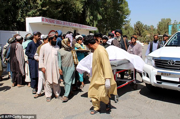 Afghan villagers carry a dead body on a stretcher outside a hospital following an airstrike in Lashkar Gah