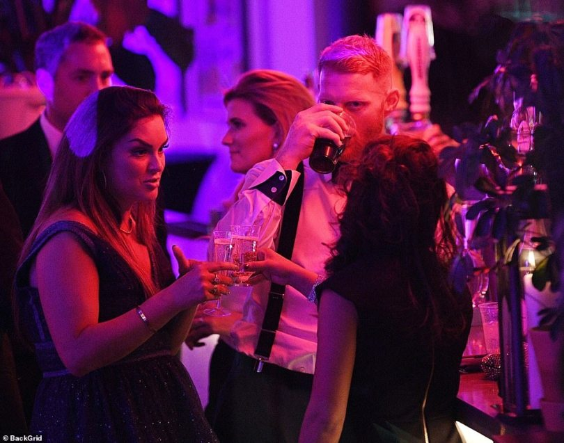 Ben Stokes enjoys a drink at the award ceremony in London on Wednesday, while his wife clinks her glass with another guest and chats after his awards victory
