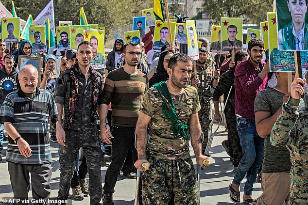 Fighters and veterans from the Kurdish women's protection units (YPJ) and the people's protection units (YPG) march inQamishli, which is one of the targets for the Turkish assault