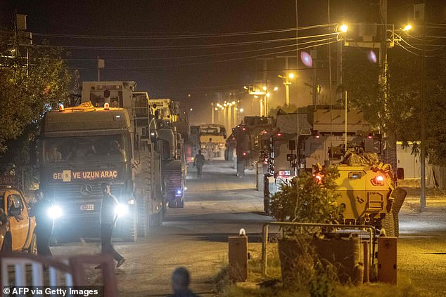 The SDF begged world leaders for help to avoid 'thousands of innocent civilians' being killed as Turkey rolled its troops into Syria (pictured, troops on the Turkish side of the border)