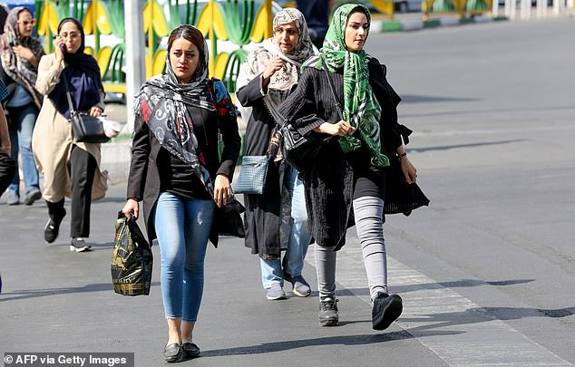 Iranian women walk in Sadeqyeh Square in the capital Tehran. After a decades long ban, football seats are finally being made open to Iranian women. The directive came after a fan dubbed 'Blue Girl' died after she set herself on fire in fear of being jailed for dressing up as a boy to attend a match