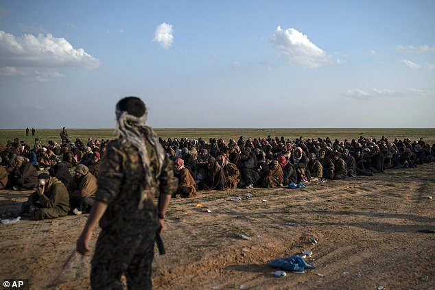 If Turkey claims all the territory currently held by the SDF then it will become responsible for between 10,000 and 15,000 ISIS fighters - 2,500 of whom are foreign-born (pictured, an SDF soldiers guards ISIS prisoners)