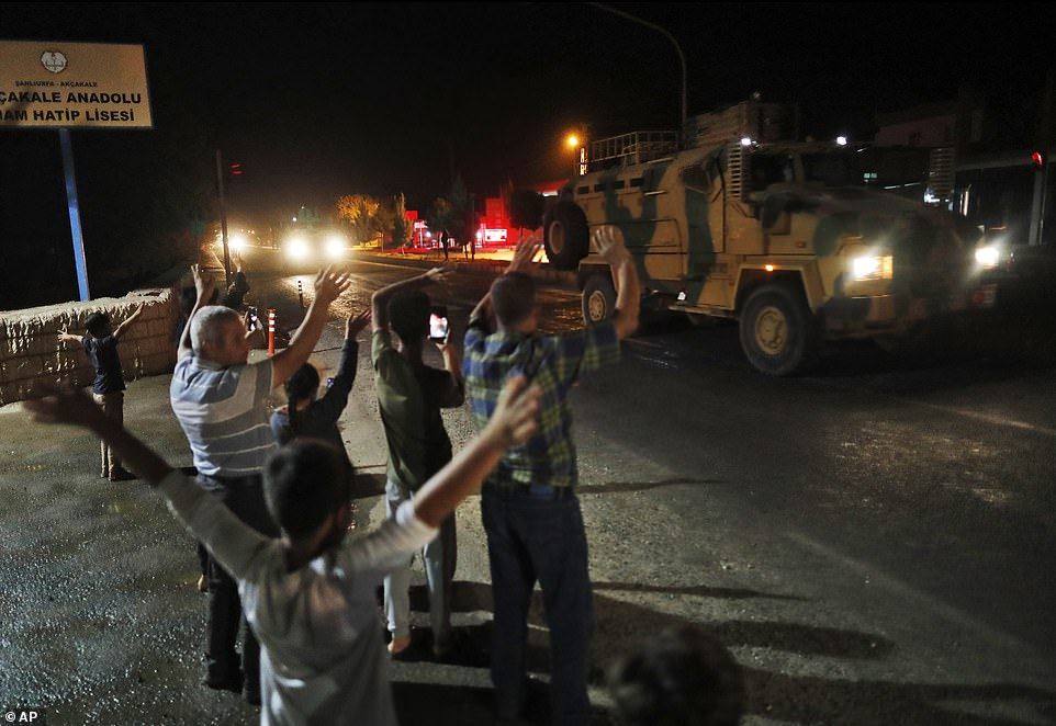 Local residents jeer and applaud as a convoy of Turkish forces vehicles and trucks carrying tanks and armoured personnel carriers is driven towards the Syrian border