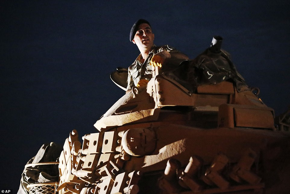 A Turkish officer sits atop this tank as it movers to its new position on the Turkish side of the border between Turkey and Syria