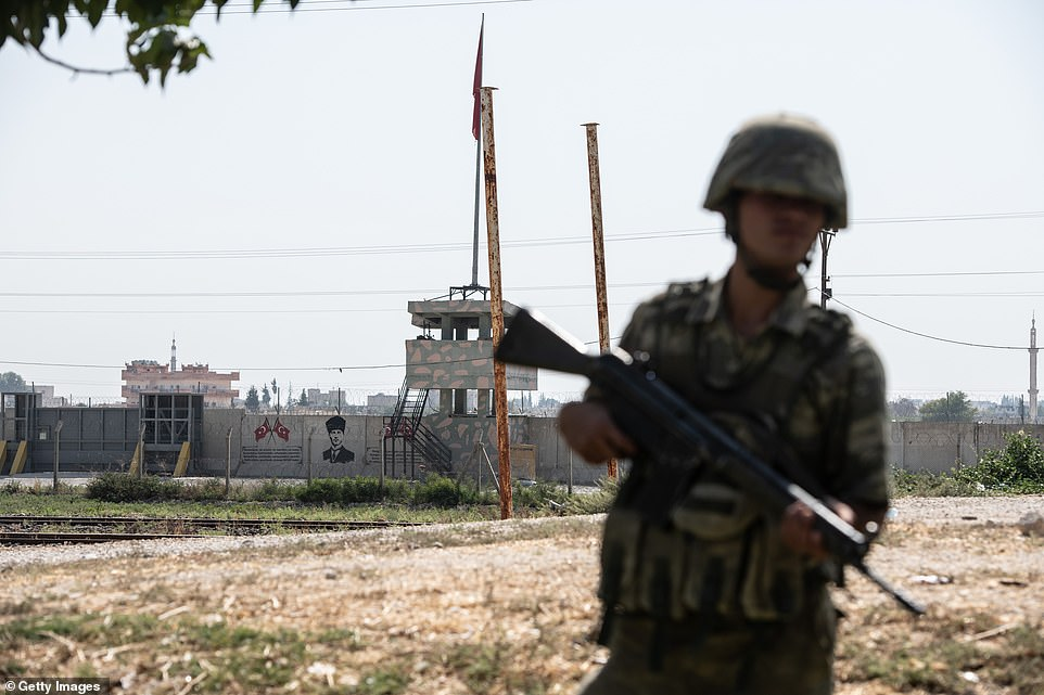 A wall separating Turkey from Syria is seen behind a Turkish soldier who stands guard in Akcakale, close to where an expeditionary force is said to have crossed into Syria early on Wednesday