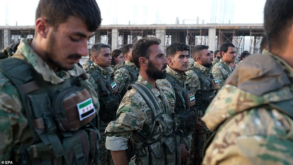Syrian National Army soldiers preparing to move to Turkey for an expected military operation by Turkey into Kurdish areas of northern Syria yesterday, in Azas near Turkish border with Syria