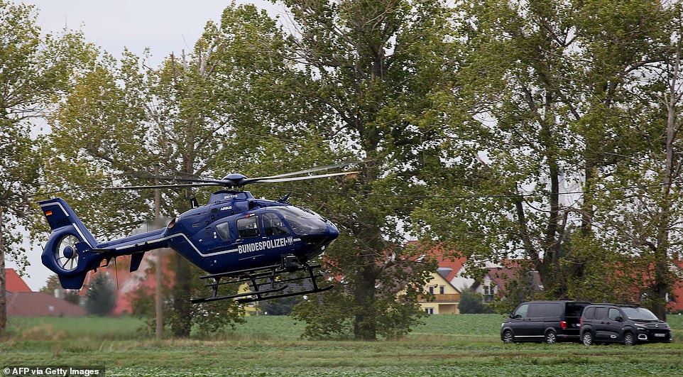A helicopter lands as police secure the area between Wiedersdorf and Landsberg near Halle, eastern Germany. Gunshots were also reported in those two towns, which sit near Halle