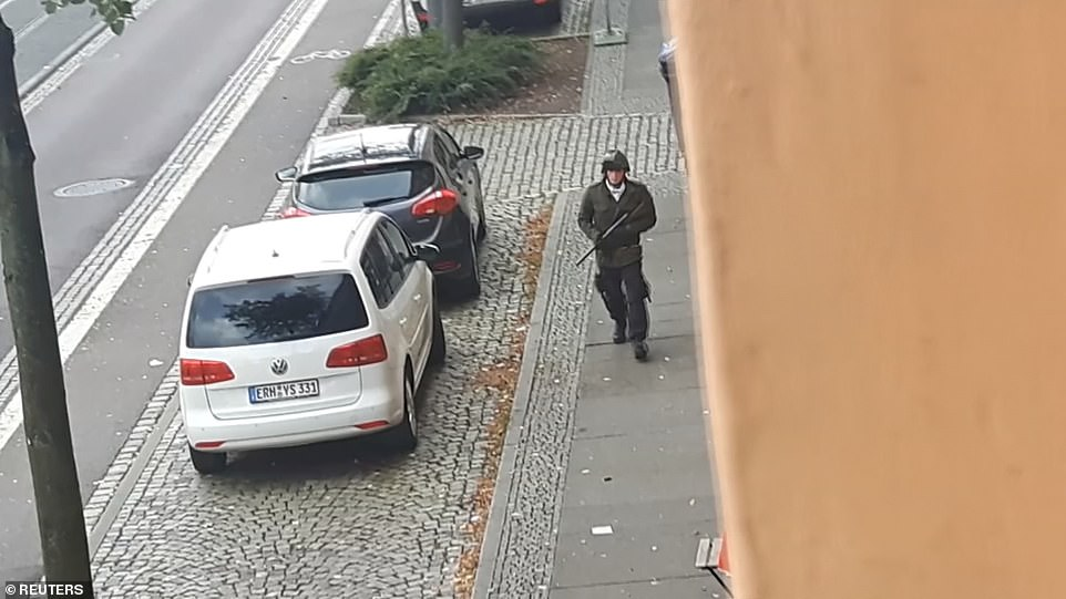 Face of the attacker: After the failed attack on the synagogue the shooters fled in a car, and then began attacking people at a nearby kebab shop (pictured, a gunman in the street near the shop)