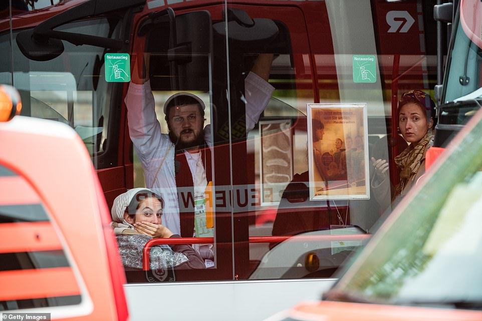 Rescued members of the Jewish community wait inside a bus near the scene of a shooting that has left two people dead