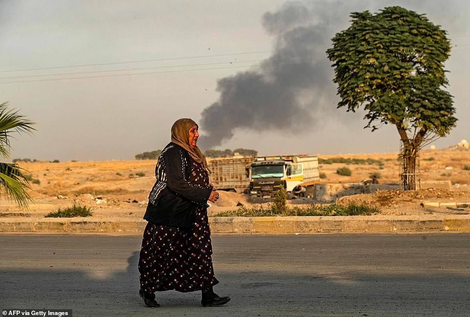 A woman walking as smoke billows behind her following Turkish bombardment in the northeastern town of Ras al-Ain in Syria's Hasakeh province along the Turkish border today