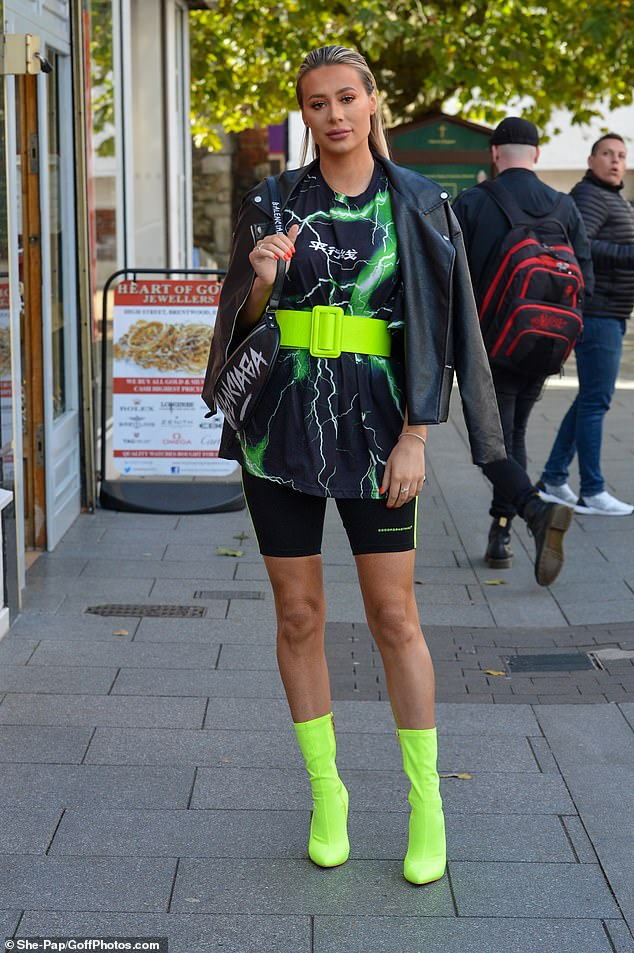 She means business: Slicking her hair back, the Celebs Go Dating star finished off her 80s inspired look with a leather jacket and Balenciaga slogan shoulder bag