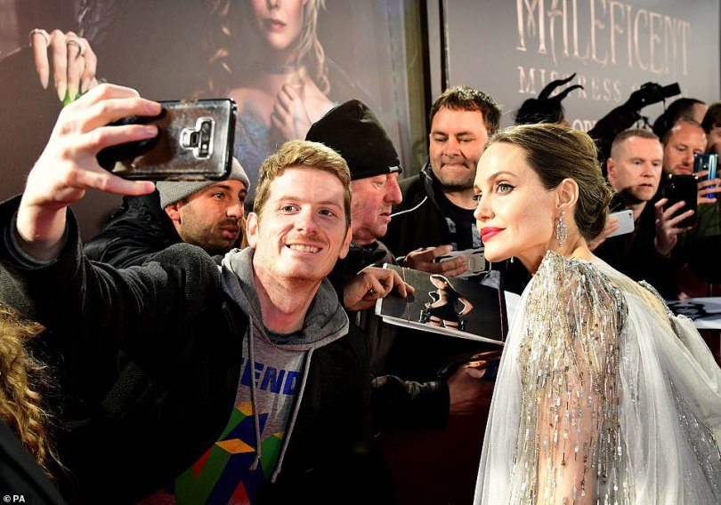 Famous: Angelina didn't break a sweat as she attended to her hoards of fans