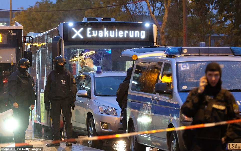 A bus whose destination board reads 'evacuation' is escorted by police past the site of a shooting in Halle on Wednesday
