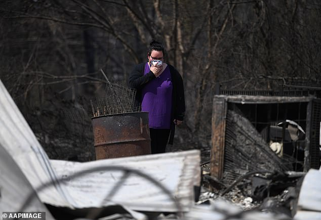 Naomi Elwell inspect the remains of her mother's house which was destroyed when the fire arrived with such speed there was simply no time for a proper evacuation of the town