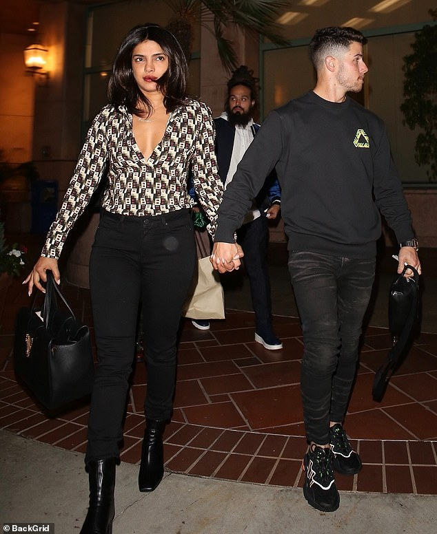 Couple: The actress, 37, flashed cleavage in a long-sleeved patterned top that she paired with black jeans. The musician, 27, wore a logo'd sweatshirt and faded jeans along with trainers